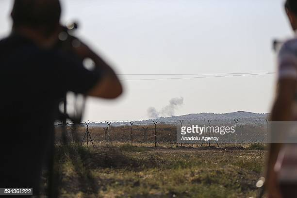 A photo taken from Turkey shows that smoke rises over Syrian side after Turkish Army's tanks and artilleries hits the Daesh positions in southeastern...