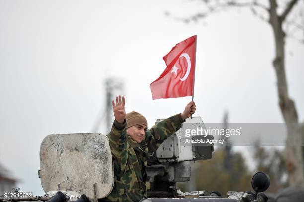 A photo taken from Turkey's Hatay shows that a Turkish soldiers gestures and holds a Turkish flag as military vehicles arrive at Kirikhan district of...