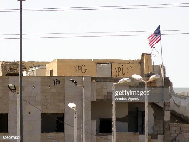 A photo taken from Turkey's Sanliurfa district shows an American flag flying on top of a custom house at the entrance of Tel Abyad district Raqqa...