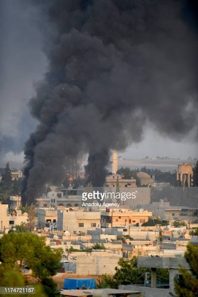 Photo taken from Turkey's Sanliurfa province, on October 09, 2019 shows smoke rises at the site of Ras al-Ayn city of Syria as Turkish troops along...