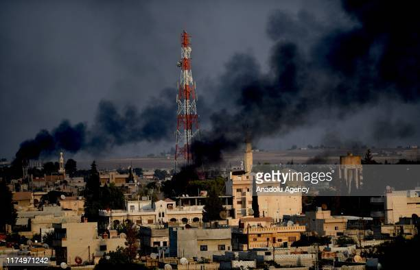 Photo taken from Turkey's Sanliurfa province, on October 10, 2019 shows dark smoke rises in Syria's Rasulayn town after terrorists burn tires to...