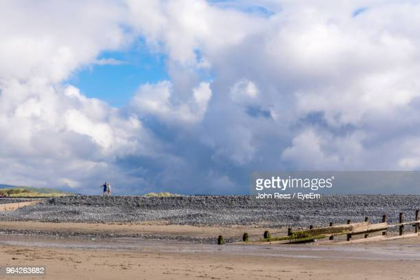 Distant View Of Couple At Beach Against Cloudy Sky