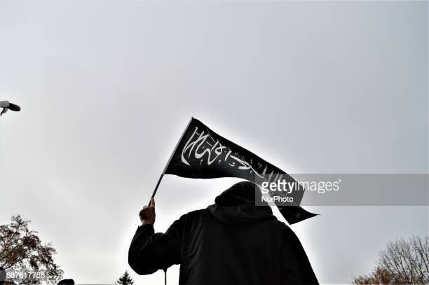A photo taken in Ankara Turkey on December 7 2017 shows a protester waving a black flag with Arabic letters as Turkish Muslims take part in a protest...