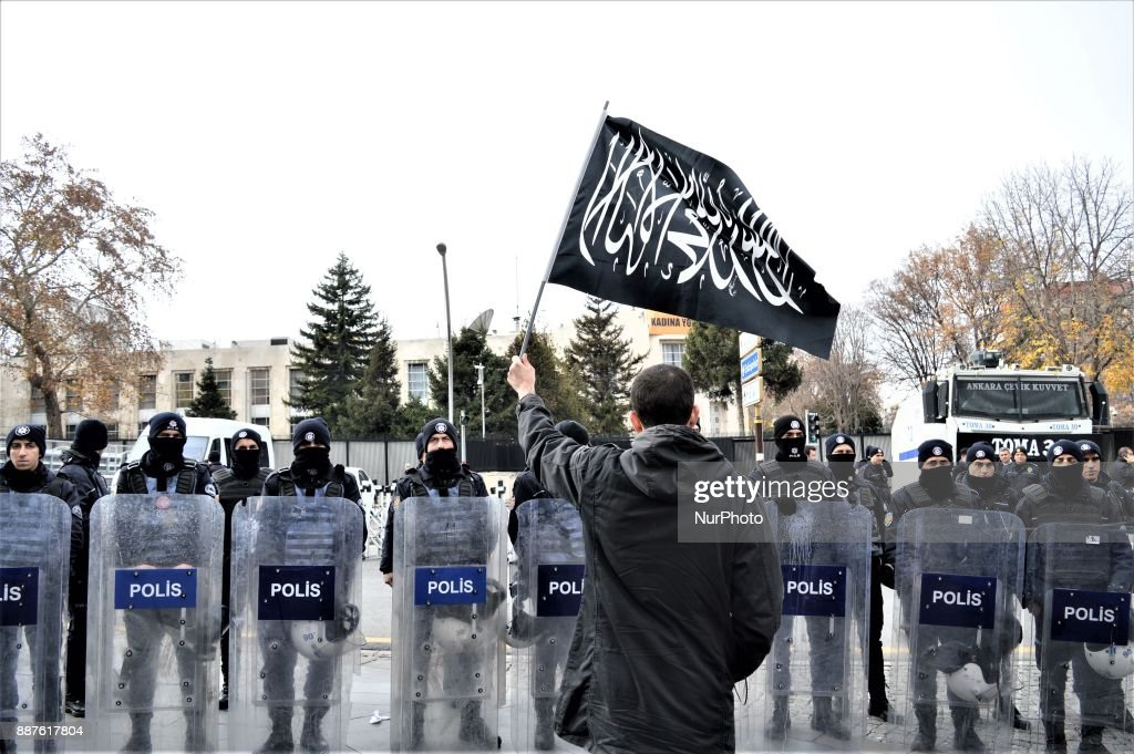 A photo taken in Ankara, Turkey on December 7, 2017 shows a protester waving a black flag with Arabic letters in front of Turkish riot policemen as Turkish Muslims take part in a protest near the U.S. Embassy against its president Donald Trump's officially recognition the city of Jerusalem as the capital of Israel on December 6.