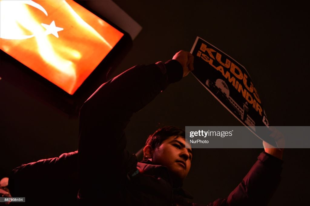 A photo taken in Ankara, Turkey on December 7, 2017 shows a protester holding a placard Turkish Muslims take part in a protest near the U.S. Embassy against its president Donald Trump's official recognition the city of Jerusalem as the capital of Israel on December 6.