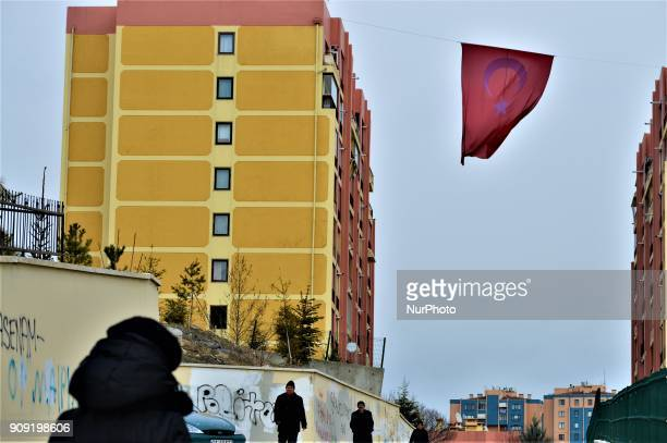 A photo taken in Ankara Turkey on January 23 2018 shows people walking under a giant Turkish national flag posted in support of Turkish soldiers...