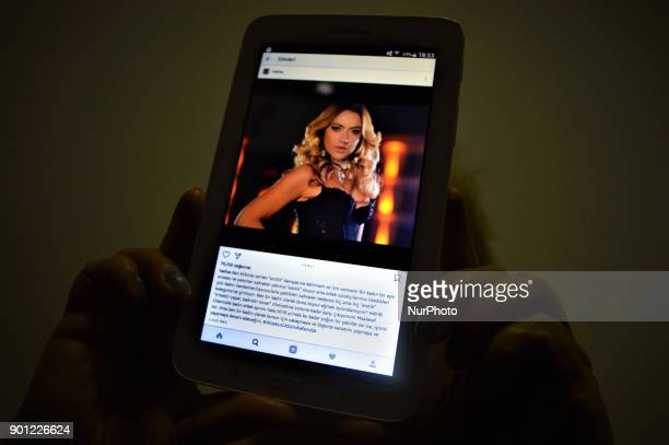 A photo taken in Ankara Turkey on January 4 2018 shows that a woman holds up a tablet displaying a picture from Belgianborn Turkish popsinger Hadise...