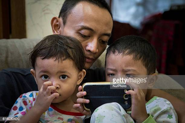 Photo taken in Depok Indonesia on 12 July 2016 show a father with his two children together checking an internet form mobile phone device Preventing...