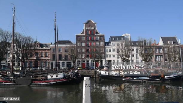 sailboats moored on river by buildings against sky - dordrecht stock pictures, royalty-free photos & images