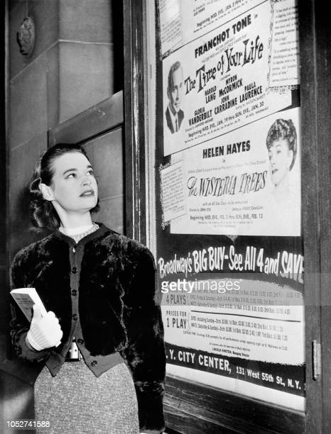 """Photo taken in January 1955 shows US actress and fashion designer Gloria Vanderbilt posing next the poster of the play """"The time of your life"""" at the..."""