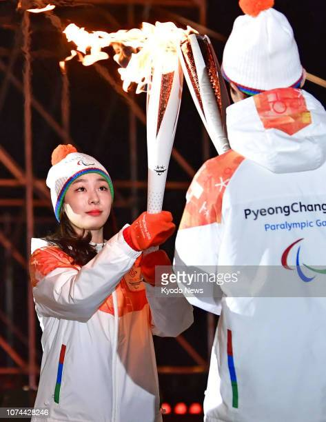 Photo taken in March 2018 shows Kim Yu Na the 2010 Vancouver Olympic figure skating champion passing the flame during the torch relay for the...