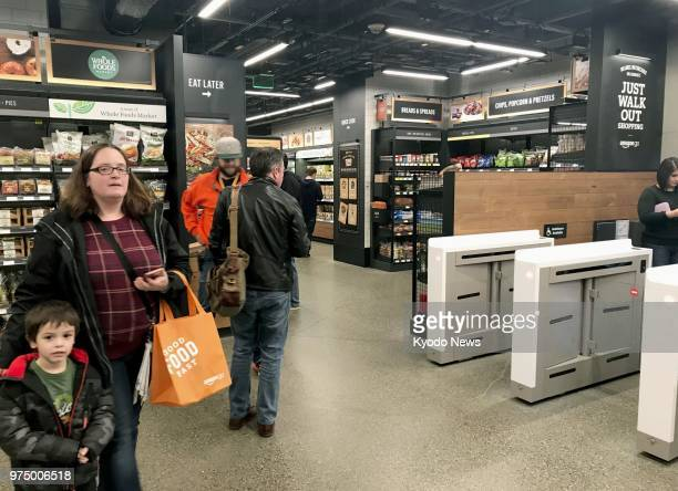 Photo taken in March 2018 shows shoppers at a checkoutfree Amazon Go grocery store in Seattle The store operated by online retailer giant Amazoncom...
