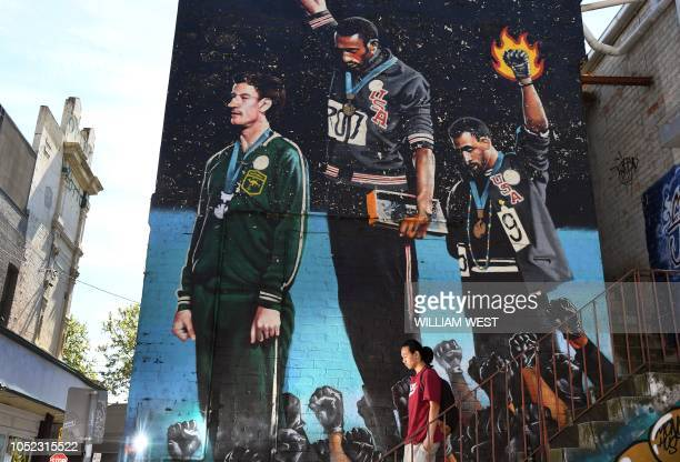 Photo taken in Melbourne on October 8 shows a man walking past a giant mural of Australian runner Peter Norman with US sprinters Tommie Smith and...