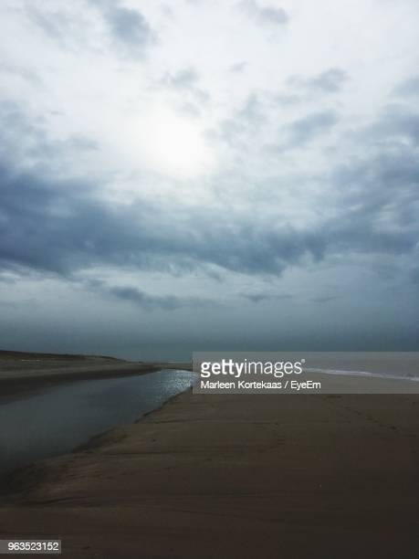 scenic view of beach against sky - horizon over water stock photos and pictures
