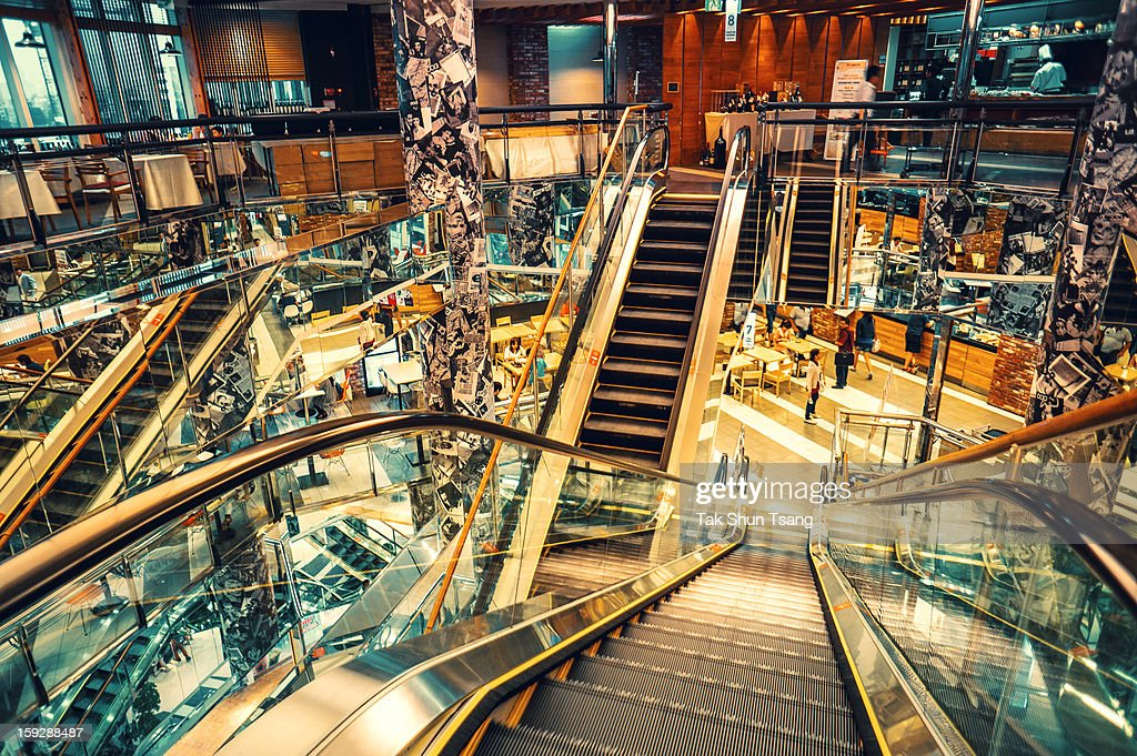CONTENT] Photo taken in one of the shopping mall in seoul. Escalators are running slowly across levels. Portrait photos on pillars create a busy composition.