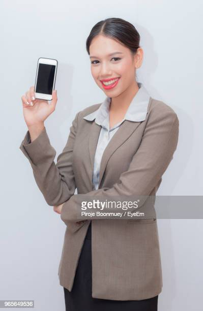 Portrait Of Smiling Businesswoman Showing Mobile Phone While Standing Against White Background