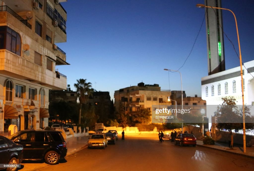 A photo taken in the early hours of April 14, 2018 shows men leaving a mosque in Damascus' Mazze neighbourhood after the daybreak Muslim prayer, following strikes by the US, France, and Britain against the Syrian government. Western strikes early Saturday hit Syrian military bases and research centres in and around the capital and the country's centre, a monitor said, as the US, France, and Britain announced a joint operation. /