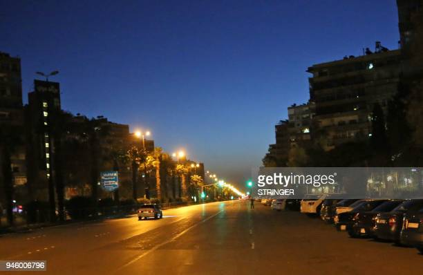 TOPSHOT A photo taken in the early hours of April 14 2018 shows slow traffic on a main avenue in Damascus' Mazze neighbourhood after the US France...