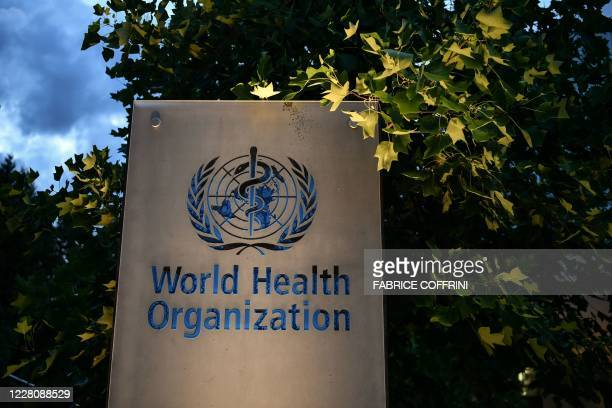 Photo taken in the late hours of August 17, 2020 shows a sign of the World Health Organization at their headquarters in Geneva amid the COVID-19...