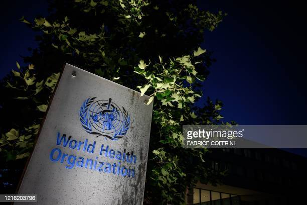 Photo taken in the late hours of May 29, 2020 shows a sign of the World Health Organization at their headquarters in Geneva amid the COVID-19...