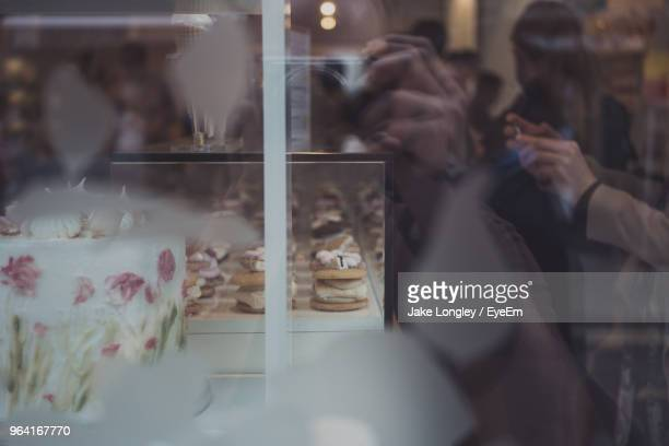 Reflection Of People On Glass By Dessert In Display Cabinet At Bakery Shop