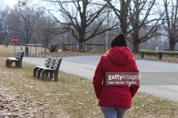 Rear View Of Woman Walking On Field During Winter
