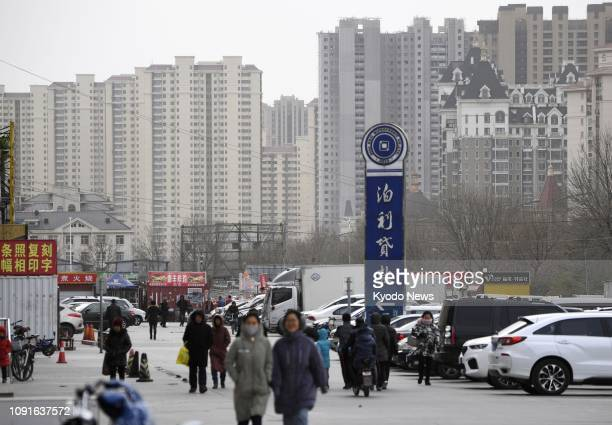 Photo taken Jan. 31 shows people walking on a street in Yanjiao, a commuter town for Beijing, with high-rise condominiums seen in the background....