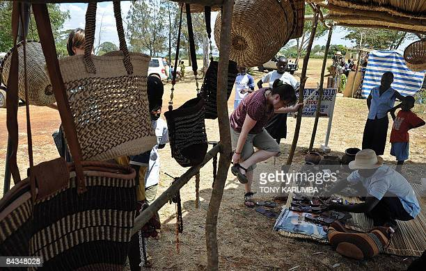 TOURISM Photo taken January 18 2009 shows tourists shopping in a stall selling Obamarelated merchandise at Nyang'oma village Kogelo during...