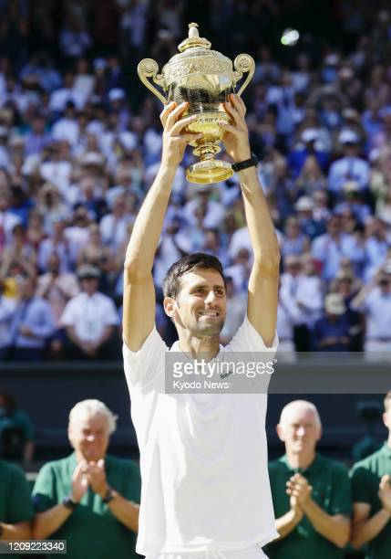Photo taken July 15 shows Novak Djokovic of Serbia holding up his trophy after winning the Wimbledon tennis tournament in London