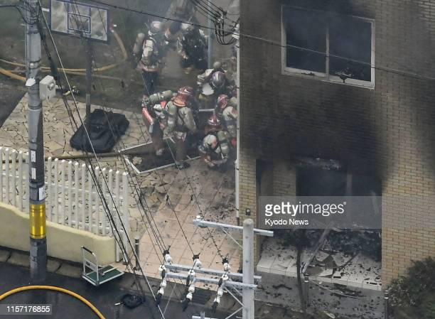 Photo taken July 18 from a Kyodo News helicopter shows firefighters at a Kyoto Animation Co studio in Kyoto western Japan after a man set the...