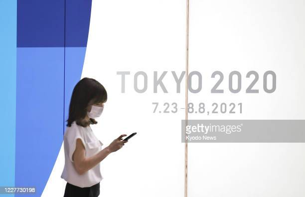 Photo taken July 22 near the Tokyo metropolitan government building shows a poster promoting the Tokyo Olympics, rescheduled to 2021 due to the...