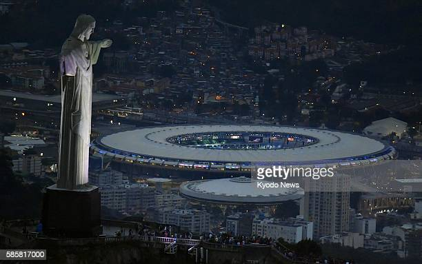 Photo taken July 22 shows the Christ the Redeemer statue atop the Corcovado mountain overlooking the Maracana Stadium where the opening ceremony...