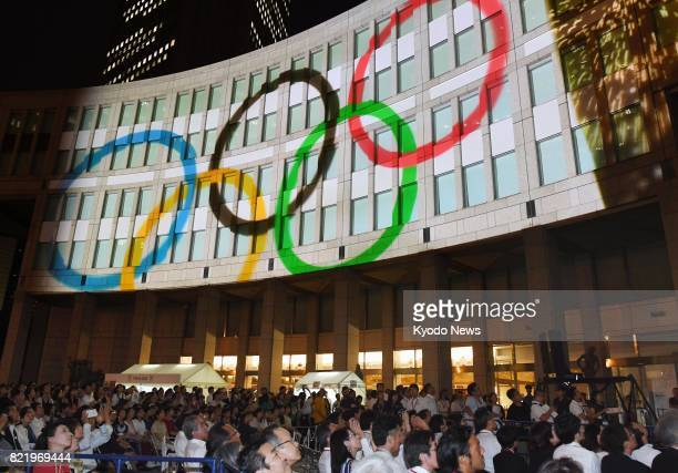 Photo taken July 24 shows the Olympic rings projected during an event held in front of the Tokyo metropolitan government building to mark three years...