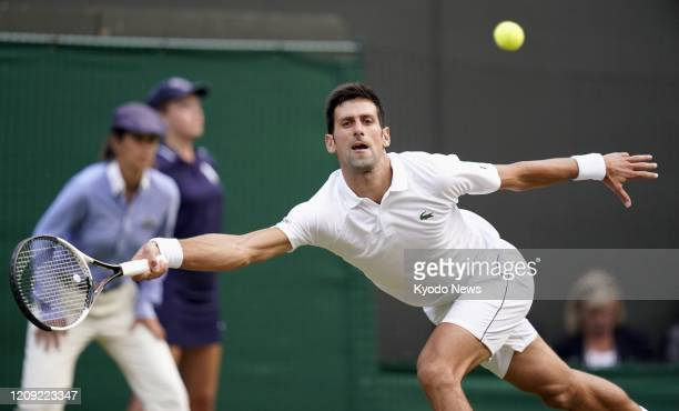 Photo taken July 9 shows Novak Djokovic of Serbia playing against Karen Khachanov of Russia in the fourth round of the Wimbledon tennis tournament in...