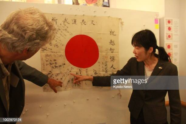 Photo taken June 25 2018 in Astoria Oregon shows Obon Society founders Keiko Ziak and her husband Rex examining a Yosegaki Hinomaru flag sent to the...