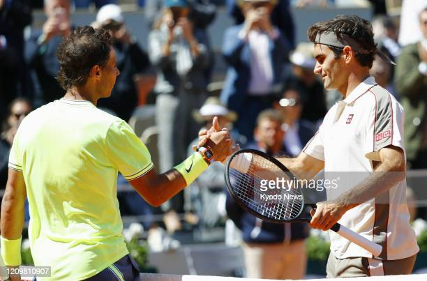 Photo taken June 7 shows Roger Federer of Switzerland shaking hands with Rafael Nadal after losing to the Spanish player in the semifinals of the...