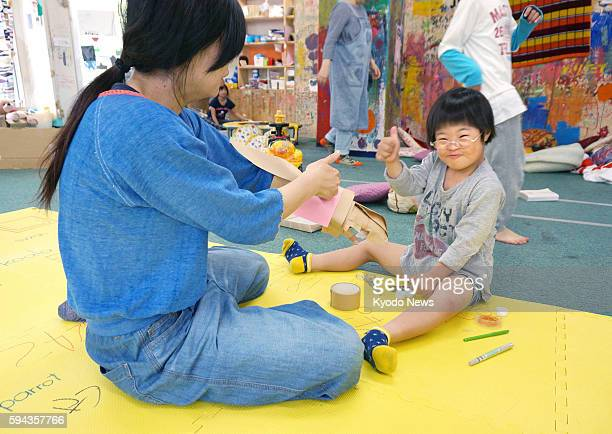 Photo taken May 21 in Hiroshima shows an elementary school student with an intellectual disability working on an art piece at afterschool daycare...