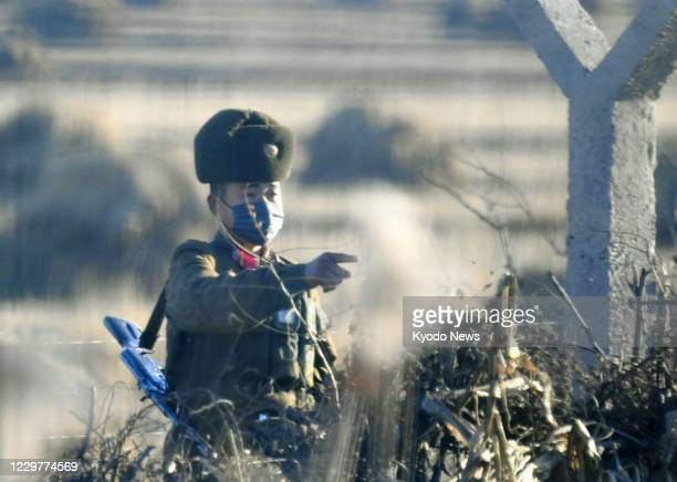 Photo taken Nov. 13 from the Chinese border city of Dandong shows a North Korean soldier standing guard on Hwanggumpyong Island in the Yalu River.