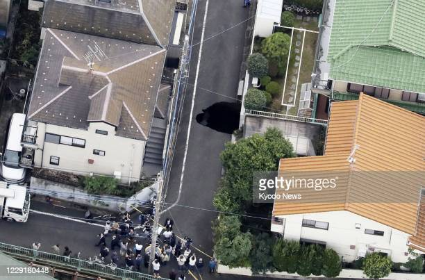 Photo taken Oct. 18 from a Kyodo News helicopter shows a sinkhole about 5 meters in length, 2.5 meters in width and 5 meters in depth on a road in a...