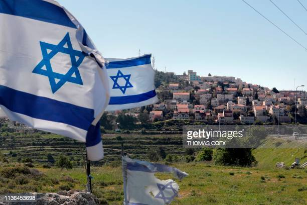 A photo taken on April 12 2019 shows Israeli flags in front of a partial view of the Israeli settlement of Efrat situated on the southern outskirts...