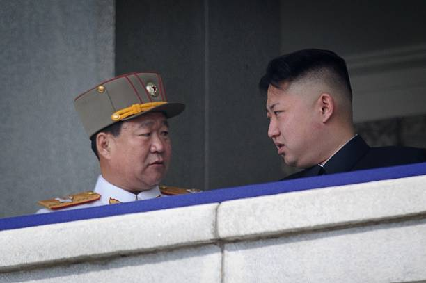 A photo taken on April 15, 2012 shows a man believed to be Choe Ryong-Hae (L) talking with North Korean leader Kim Jong-Un (R) attending a military parade in Pyongyang