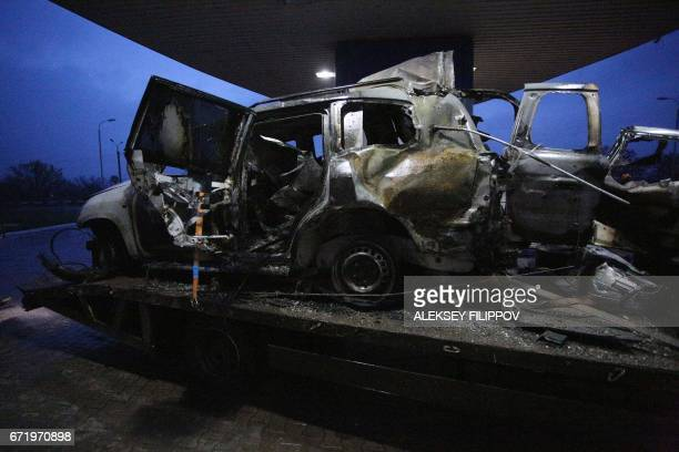 A photo taken on April 23 2017 shows an OSCE mission patrol vehicle destroyed as a result of an explosion being towed not far from Lugansk Ukraine on...