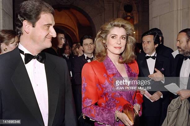 A photo taken on April 25 1989 shows French actress Catherine Deneuve flanked by her companion President of Canal Plus Pierre Lescure at the Garnier...