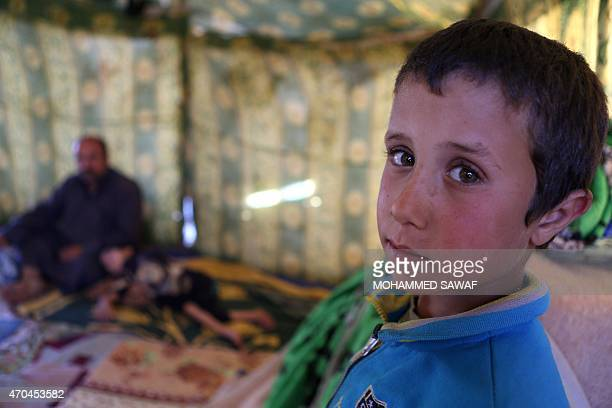 A photo taken on April 5 2015 shows a displaced Iraqi boy posing for a photo at a camp for internally displaced people in the northern city of...