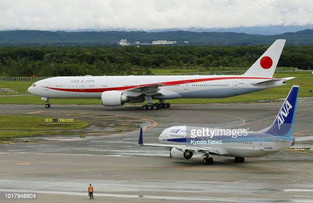 Photo taken on Aug 17 shows a new Japanese government jet a Boeing 777300ER near an All Nippon Airways Co plane at New Chitose Airport in Hokkaido...