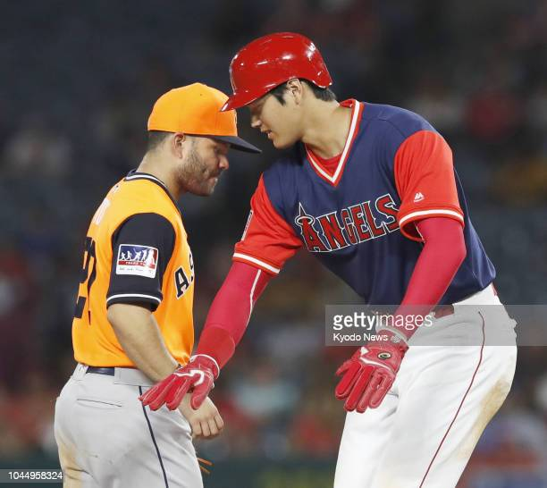 Photo taken on Aug 25 shows Shohei Ohtani of the Los Angeles Angels reaching out to Jose Altuve of the Houston Astros during the eighth inning of a...