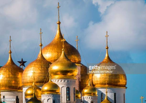 A photo taken on August 08 2017 shows one of the Kremlin's ruby stars seen behind the golden domes of the Annunciation Cathedral the Kremlin in...