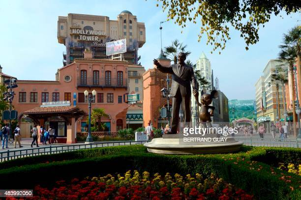 A photo taken on August 13 2015 shows a statue of Walt Disney and Mickey Mouse and the Hollywood Tower attraction at the Walt Disney Studios park in...