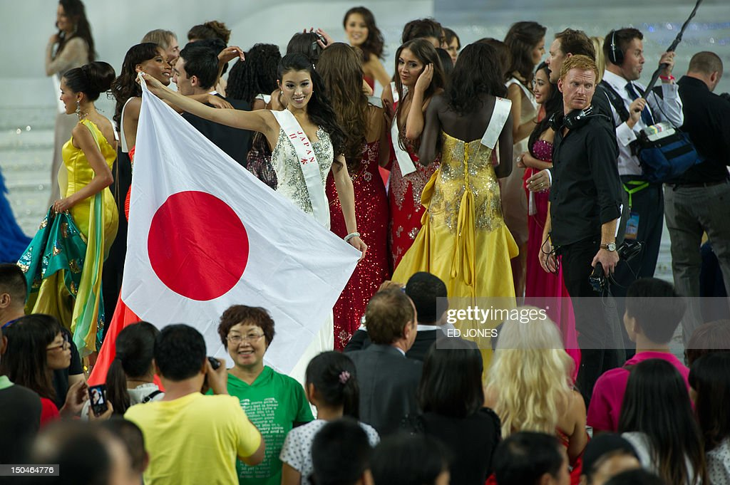 A photo taken on August 18, 2012 shows Miss Japan Nozomi Igarashi (C) holding a Japanese flag as she poses for photos following the Miss World final ceremony at the Dongsheng stadium in the inner Mongolian city of Ordos. China's Yu Wenxia of China defeated more than 100 other hopefuls at the glittering ceremony held in the Chinese mining city of Ordos, on the edge of the Gobi desert. AFP PHOTO / Ed Jones