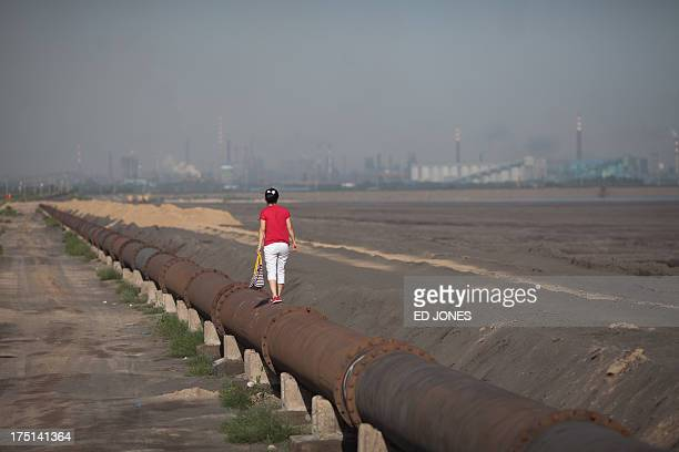 Photo taken on August 19, 2012 shows a woman standing on the banks of a 'toxic lake' surrounded by rare earth refineries near the inner Mongolian...